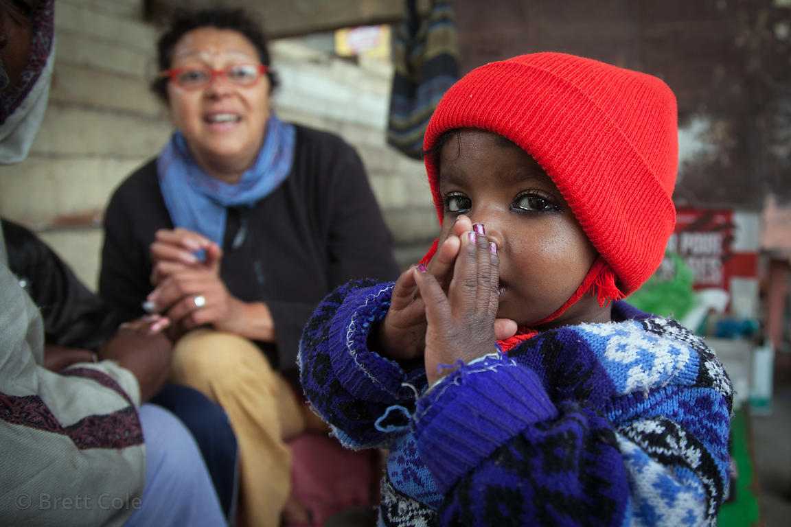 "A typically adorable toddler watches as a nurse from the French NGO Agir pour Benares tends to a girl with a ""black-eye"" at a..."
