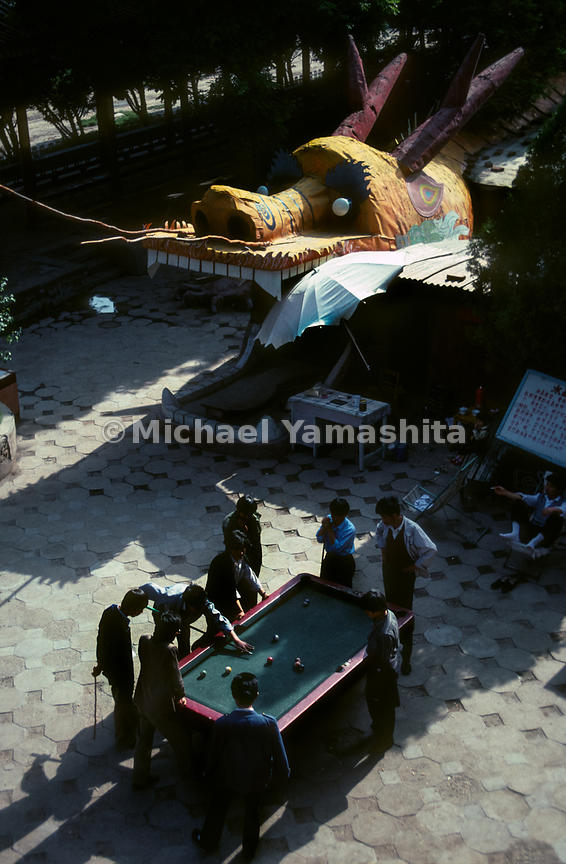 Men play pool near a dragon head. Lanzhou, China