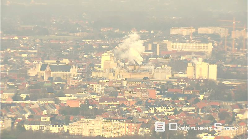 Past steaming factories and medieval architecture in Aalst, Belgium town hall and belfry at left, midframe