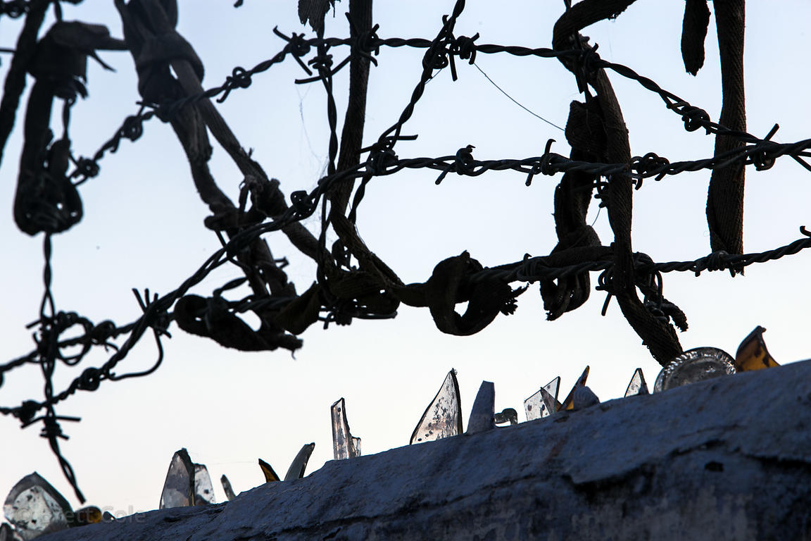 Barbed wire and glass shards on a wall in Pushkar, Rajasthan, India