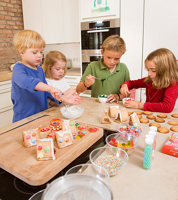 four kids baking cookies