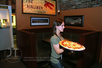 Server Erin Beal delivers pizza to a table at the Airliner Bar, 22 S Clinton Street in downtown Iowa City Saturday night. Cop...