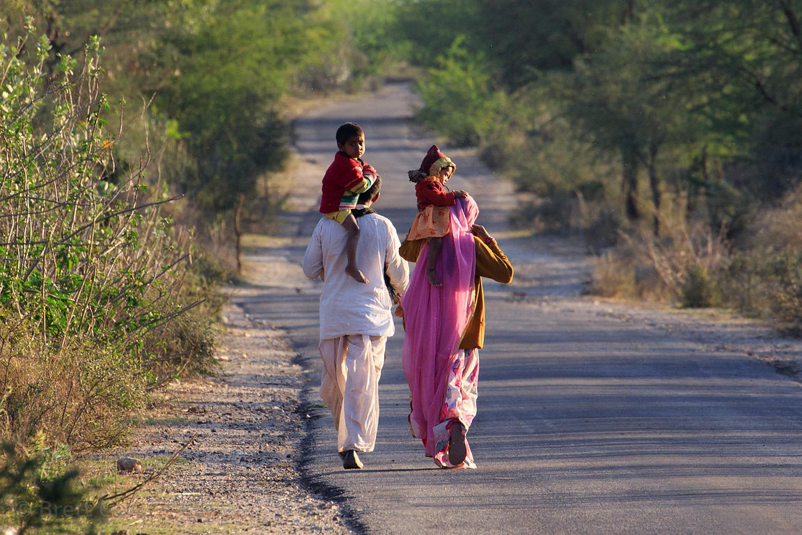 A family walk down a deserted road near Sidiyas village, Rajasthan, India