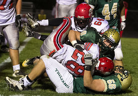 Iowa City West's Ezra Reiners (9) and Ben Hilmer (56) tackle Iowa City High's Bryson Runge (28) during the Battle for the Boo...