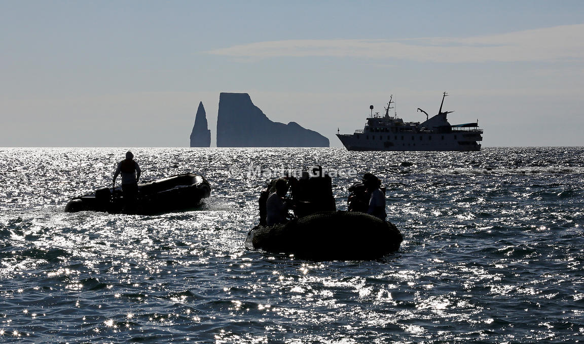 Kicker Rock and tourist ship M/V La Pinta behind two tourist Zodiac inflatables, photographed contra jour, Cerro Brujo, San C...