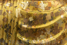Gold leaf placed on a statue by worshipers at the Wat Arun temple in Bangkok, Thailand.
