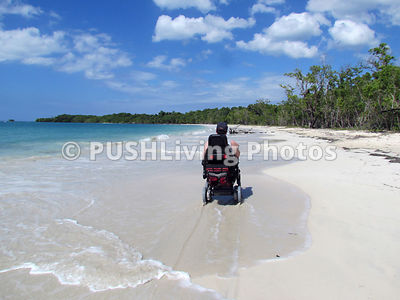 Man in a power chair on a beautiful white tropical ocean beach