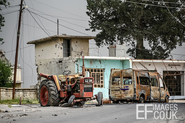 A burned out tractor and van abandoned in front of a bullet riddled home on the streets of Badush during its liberation from ...