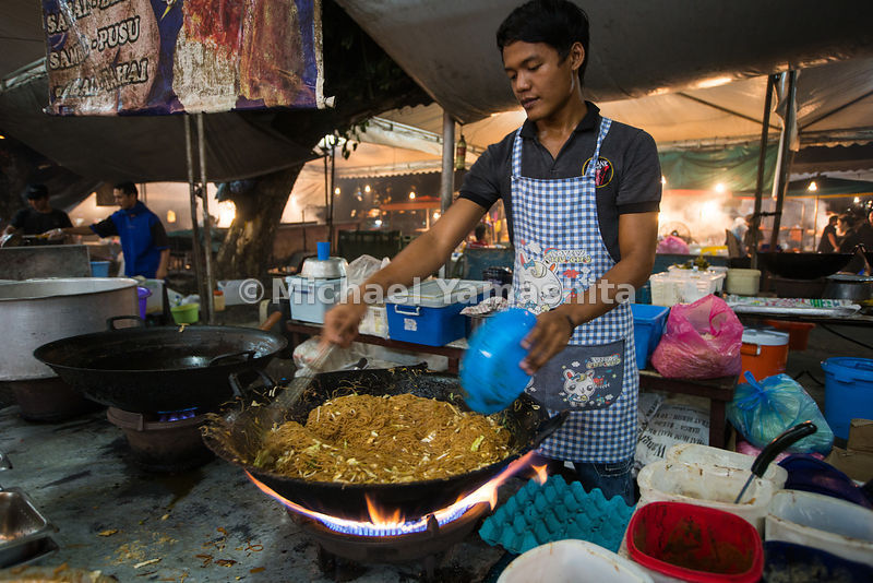 Chef cooks a stir fry in a large bowl. Tasek Merimbun Lake
