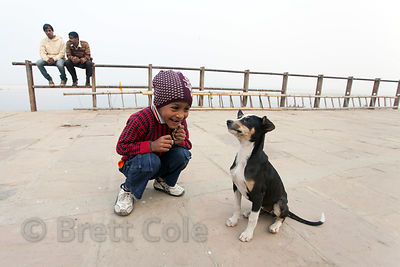 A boy plays with a stray dog puppy near Assi Ghat, Varanasi, India.