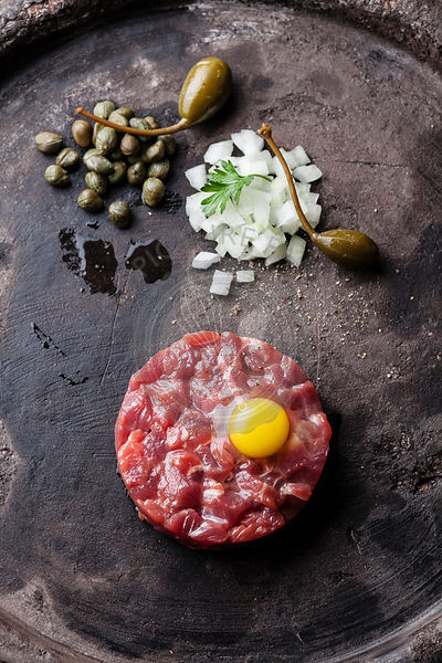Beef tartare with capers and fresh onions on dark background