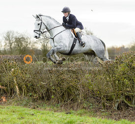 Caroline Edwards jumping a hedge on Graham Smith's