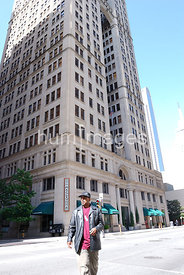 Man walking in front of the Magnolia Hotel in downtown Dallas, Texas