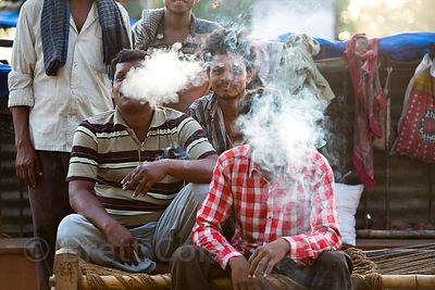 Three men smoke cigarettes near Jama Masjid mosque in Delhi, India. The area already has extremely bad air pollution.