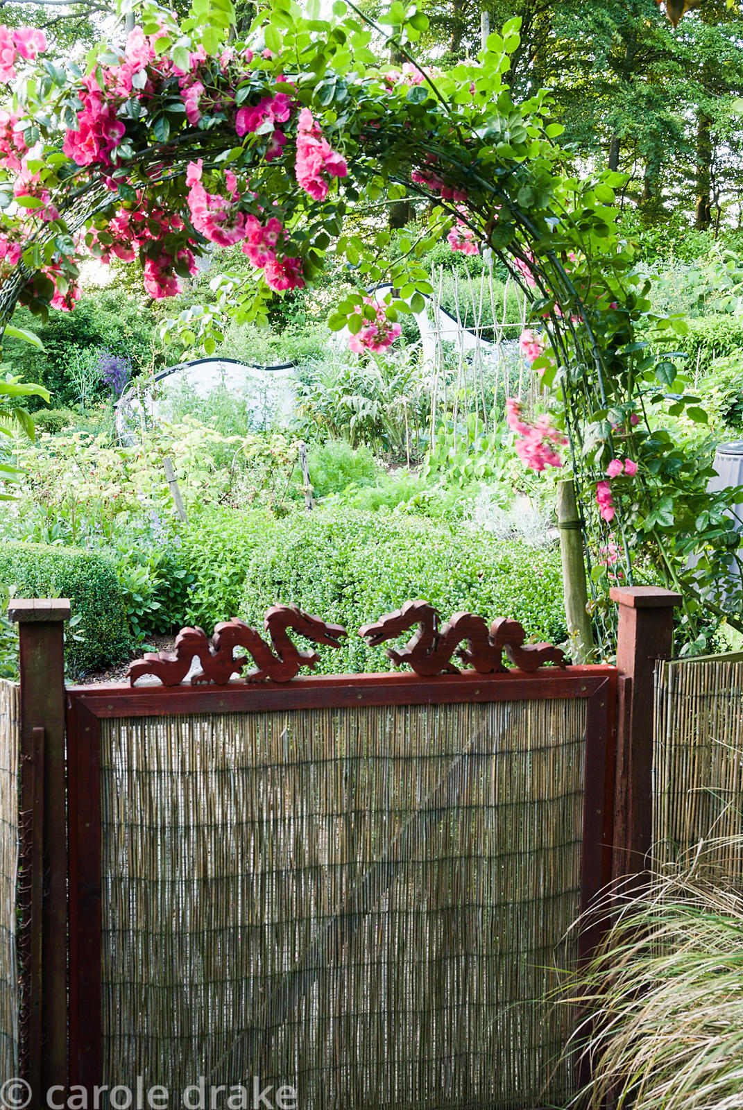Gate into the kitchen garden is decorated with small carved dragons and framed with an arch of pink roses. Beggars Knoll, New...