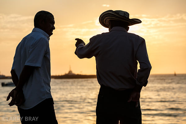 2 local men chatting at sunset in Santa Marta, Colombia, South America
