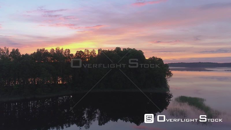 Reveal shot of a calm and reflective lake during sunrise. Latvia