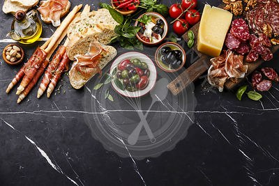 Italian snacks food with Ham, Sliced bread Ciabatta, Olives, Parmesan cheese, Grissini bread sticks, Feta cheese with dried tomatoes and Sausage on dark marble background copy space