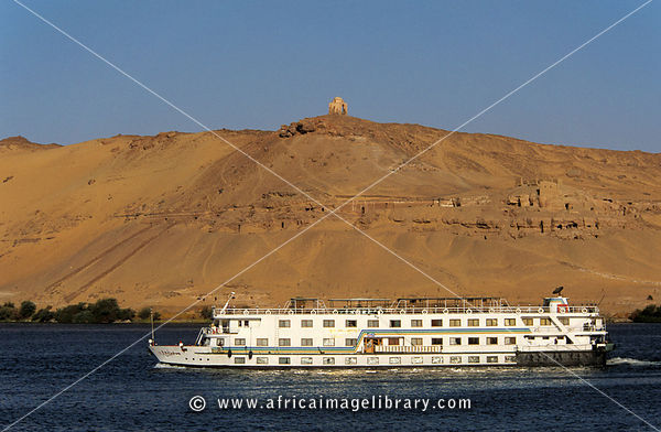 Nile Cruise boat with 'Tombs of the Nobles' in the cliffs in the background, Aswan, Egypt