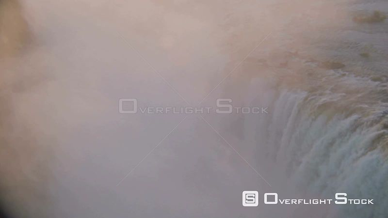 Aerial lens flare waterfall flowing over lip of rockface, sun reflecting on mist in gorge at sunset sunrise Victoria Falls Zi...