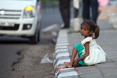 A girls sits unattended on the curb of Purandare Rd., a heavily trafficked road along Chowpatty Beach in Mumbai, India.
