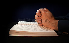 Clasped hands on a bible while praying to God.