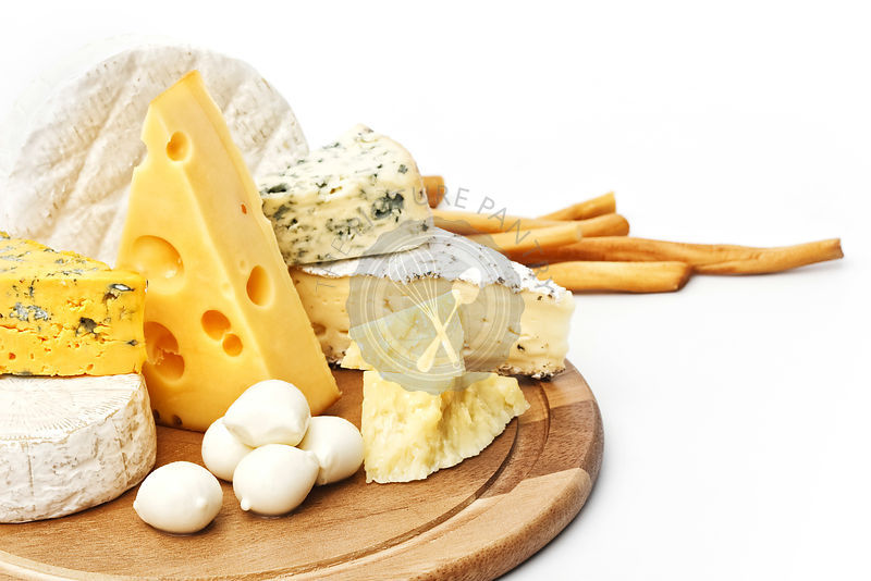 Assortment of various types of cheese on wooden board on white background