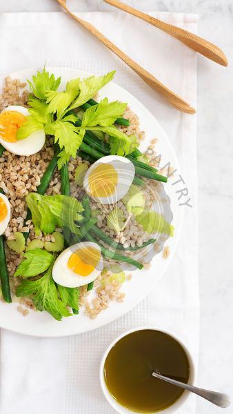 Partial view of a bean, barley and egg salad with a bowl of dressing and wooden tongs.