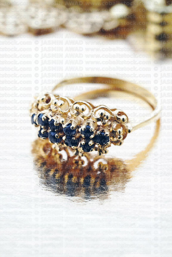 Elegant ring with sapphires with jewelry in the background