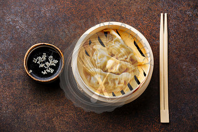 Gyoza dumpling in bamboo steamer, chopsticks and sauce on brown background