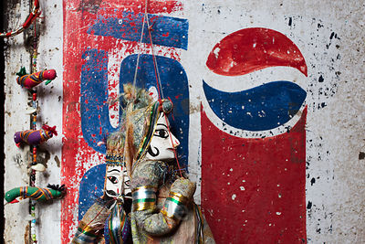A puppet sits next to a weathered Pepsi advertisement, Pushkar, Rajasthan, India