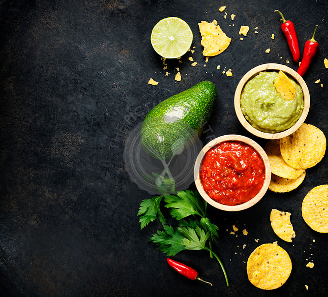 Mexican food concept: tortilla chips, guacamole, salsa and fresh ingredients over vintage rusty metal background. Top view