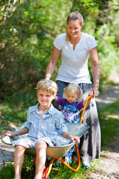 Mother pushing children in wheelbarrow