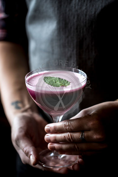 A woman is holding a blueberry cocktail in a coupe glass in her hands