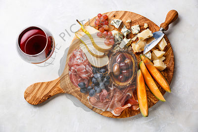 Meat and cheese plate antipasti snack with Prosciutto ham, Parmesan, Blue cheese, Cantaloupe melon and Olives