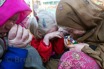 Albino sisters plays with a Rubik's cube given as a gift, Pushkar, Rajasthan, India. The family of ten albinos is panhandling...