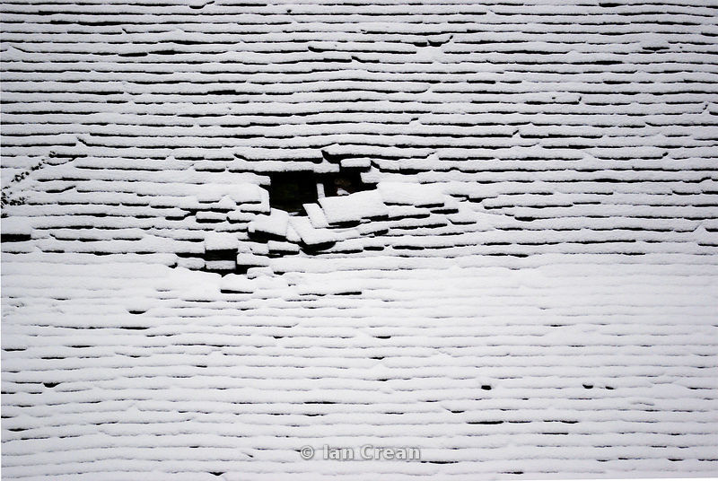 Snow on a broken slate roof