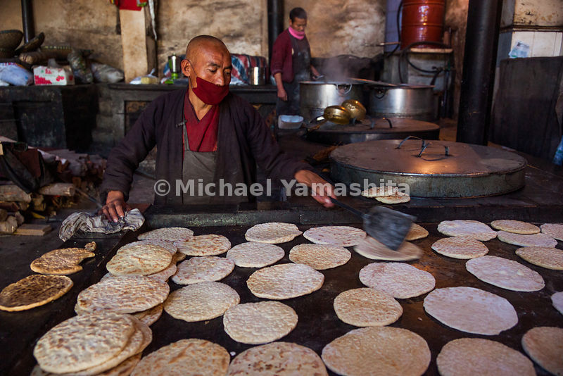 A monk in Gandze prepares the traditional flatbread of Central Tibet, called Balep Korkun. It is cooked on a griddle and made...