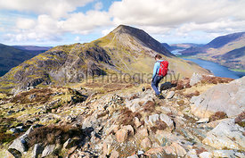 A female hiker and their dog descending a rocky path from the summit of Hay Stacks in the English Lake District.