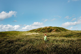 Girl with magnifying glass in Danish dunes