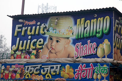 Fruit juice billboard featuring a white baby in a hat, Delhi, India