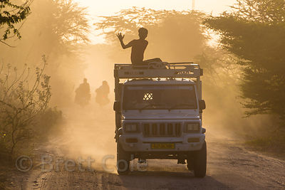 A truck carries people down a dusty country road at sunset, Maseena village, Rajasthan, India