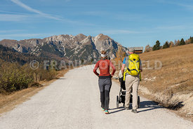 A man and woman with child in a pushchair  hiking in the Fanes Sennes Prags Nature Park near Schluderbach Carbonin in the Sou...