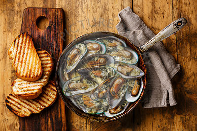 Mussels Clams Kiwi in Blue cheese sauce in cooking pan and toasted bread on wooden background