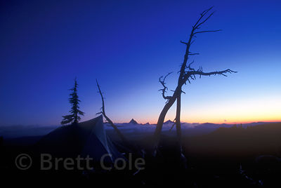 The tip of a tent mixes with the jagges summits of several Cascades snopeaks in pre-dawn light, Oregon Cascades