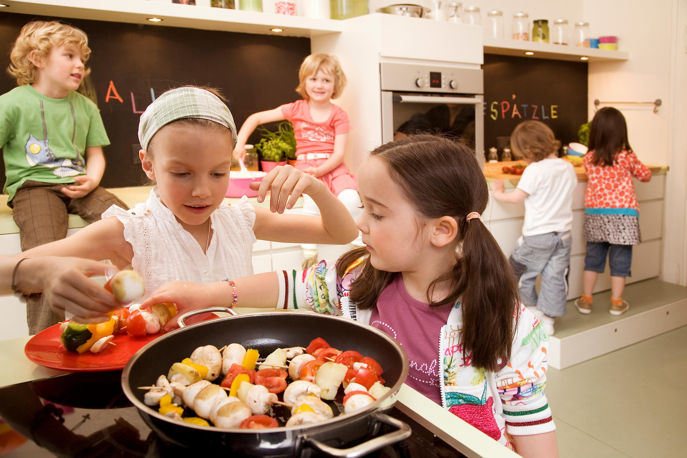 Girls and boys cooking vegetables