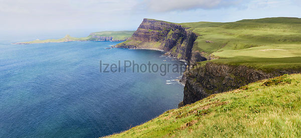 Misty Sea cliffs of Ramasaig with Neist Point in the distance. Isle of Skye, Scotland, UK.