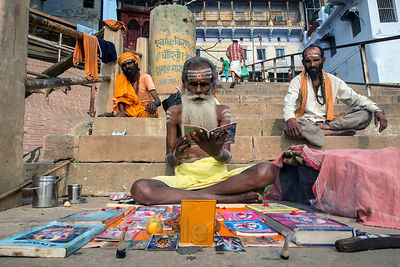 Skinny old baba reads from religious texts along the Ganges River, Meer Ghat, Varanasi, India