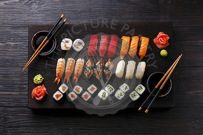 Sushi Set nigiri and rolls served on wooden serving board on black wooden background