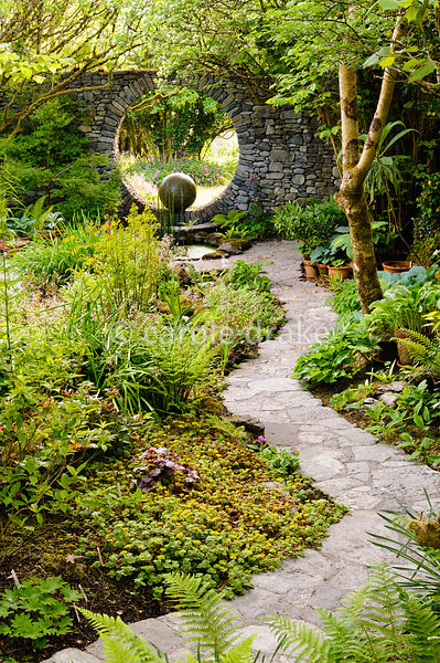 A stone path between borders of hostas and ferns leads down towards the Moon Window, a circular opening in a stone wall with ...